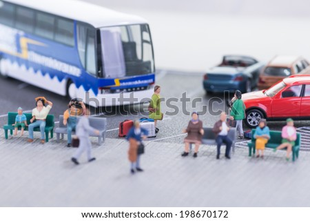 Miniature travellers at a bus station close up  - stock photo