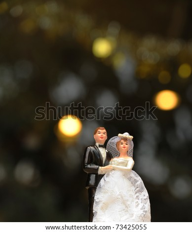 miniature wedding couple doll on dark blur background - stock photo