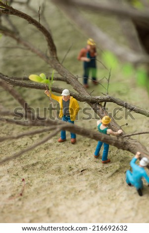 Miniature workers clearing fallen trees close up  - stock photo