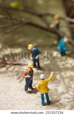 Miniature workers clearing fallen trees on a sunny day - stock photo