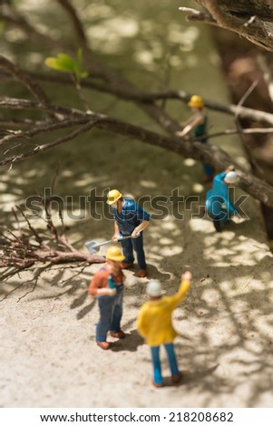 Miniature workmen clearing fallen trees - stock photo
