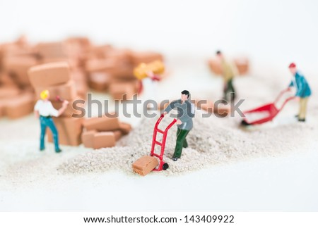 Miniature workmen laying and carrying bricks close up - stock photo