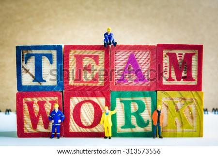 Miniature workmen with wood TEAMWORK text  - stock photo