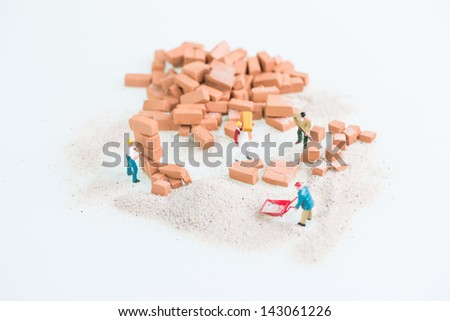 Miniature workmen working together in doing brickwork top view close up - stock photo