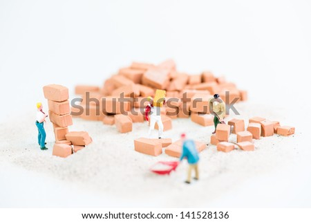 Miniature workmen working together in laying bricks with a heap of bricks background - stock photo