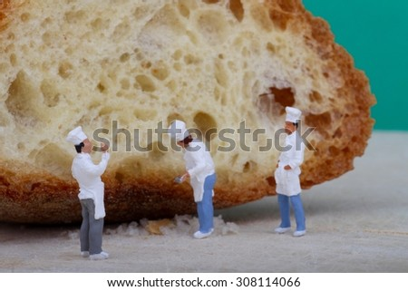 miniatures of cooks with bread on a wooden cutting board - stock photo
