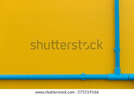 Minimalism style, Blue water pipe on yellow wall texture background. - stock photo