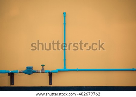 Minimalism style, Blue water pipe with faucet valve on yellow wall texture background. , process in vintage style - stock photo