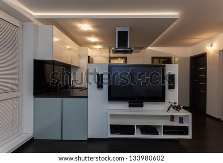 Minimalist apartment - living room with a view at kitchen - stock photo