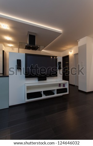 Minimalist apartment - modern appliances, big tv in living room - stock photo