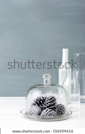 Minimalist christmas interior decoration with clear glass bottles, white pine cones and grey background, plenty of copy space - stock photo