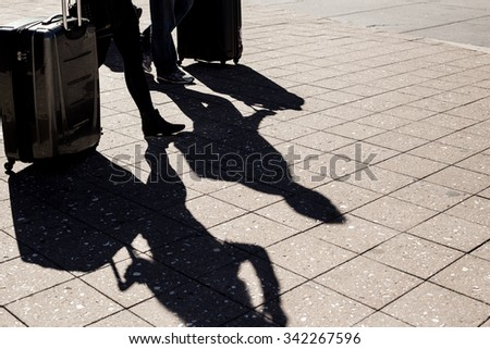 Minimalist image of two people and their shadows with suitcases walking outside - stock photo