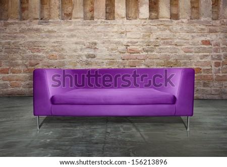 Minimalist modern purple sofa in a unusual environment antique brick wall - stock photo