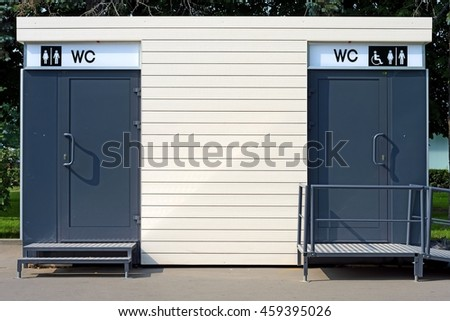 minimalistic simple portable toilet cabin with disabled access ramp and information billboard side detail exterior view