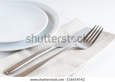 Minimalistic table setting: the white plate, fork and knife on a napkin, close-up - stock photo