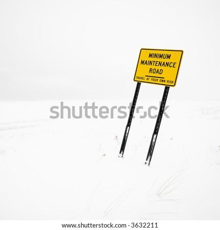 Minimum maintenance road sign in deserted winter blizzard. - stock photo