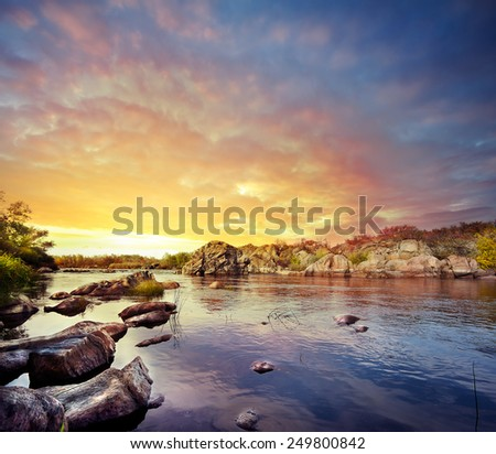 Mining fast river under dramatic sunset sky - stock photo
