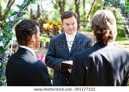 Minister performing marriage ceremony for two grooms at a gay wedding.   - stock photo