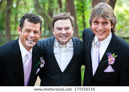 Minister posing with a handsome gay wedding couple he has just married.  *focus is on the minister. - stock photo