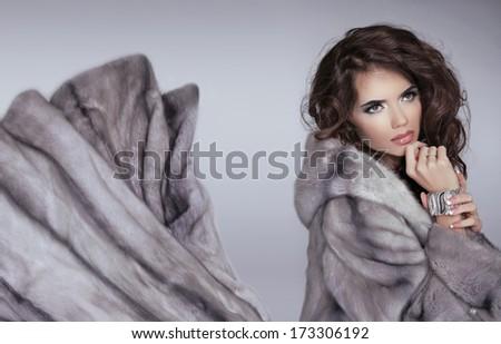Mink fur coat. Winter girl. Beautiful brunette woman isolated on grey background. Glamour Fashion Woman Portrait. - stock photo