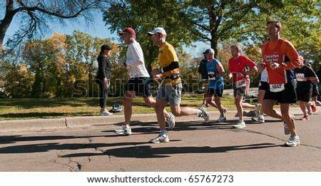 MINNEAPOLIS, MN - OCTOBER 3: Group of runners make their way up the hill at Mile 19 of the 2010 Medtronic Twin Cities Marathon, October 3, 2010 in Minneapolis, MN - stock photo