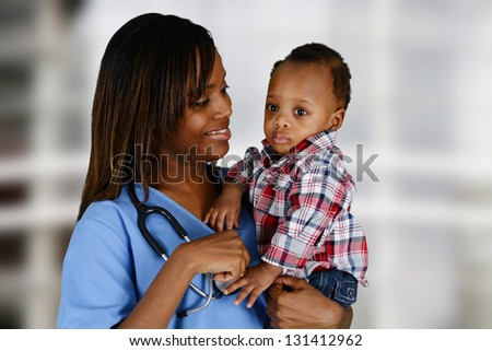 Minority nurse working at her job in a hospital with baby