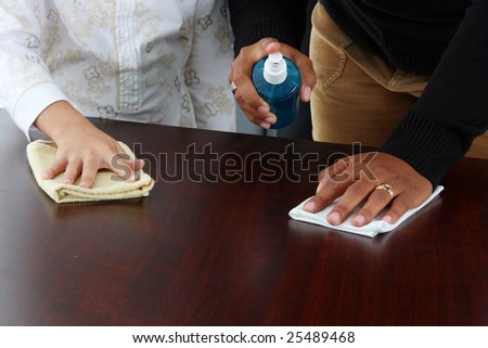 Minority woman and her daughter cleaning the table - stock photo