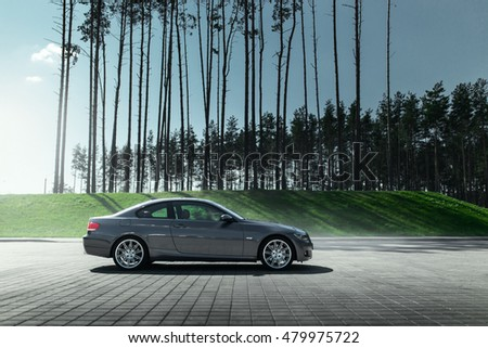 Minsk, Belarus - August 21, 2016: Car BMW Coupe E92 standing on sett empty parking lot near pine forest at daytime