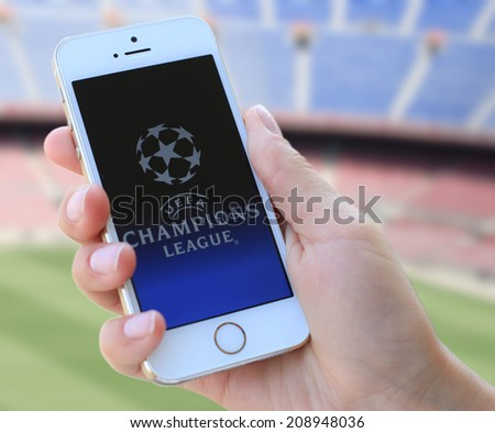 """MINSK, BELARUS - AUGUST 03, 2014: Man holding brand new white Apple iPhone 5S. The official logo of the brand """"Champions League"""". - stock photo"""