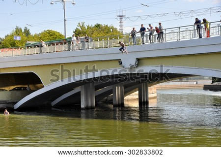 MINSK, BELARUS AUGUST 2, 2015: Unidentified person jumping from the bridge during the celebration of the Paratroopers VDV Day on 2 August 2015 in Minsk. - stock photo