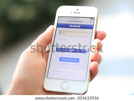 MINSK, BELARUS - JULY 05, 2014: Woman holding brand new white Apple iPhone 5S with loging in Facebook app. Facebook the largest social network in the world. - stock photo