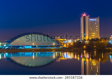 "MINSK, BELARUS - MARCH 10, 2015: Hotel Building ""Belarus"" In Old Part Minsk, Downtown Nyamiha, Nemiga View With Svisloch River, Belarus. Night Scene Street"
