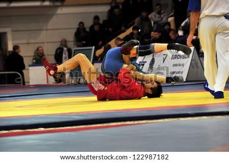 MINSK, BELARUS - NOVEMBER 10: Unidentified wrestlers fighting in the pit during SAMBO (Wrestling) WORLDCh-2012 on November 10, 2012 in Minsk, Belarus. - stock photo
