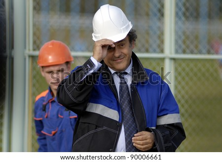 MINSK, BELARUS - OCTOBER 04: UEFA President Michel Platini(R) dons a hard hat during a construction work commencement of a building of the National Football Team Training Center on October 04, 2011 in Minsk, Belarus