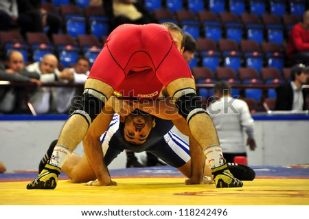 MINSK, BELARUS - SEPTEMBER 16: Unidentified wrestler (RED) in the dangerous position during Grand Prix for the prizes A.Medved in freestyle wrestling on September 16, 2012 in Minsk, Belarus. - stock photo