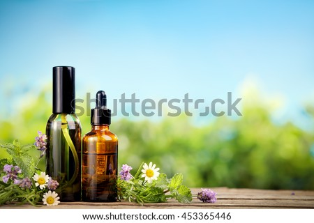 Mint essential oil in small brown bottles and fresh mint  - stock photo