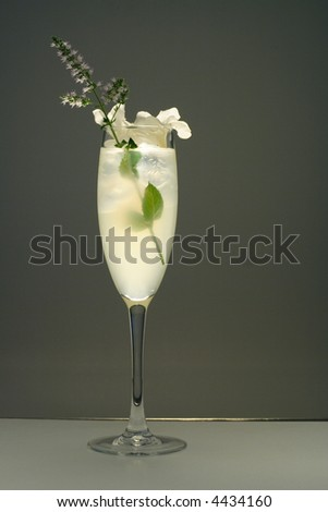 Mint flower decorated wine glass filled with white cocktail and ice - stock photo