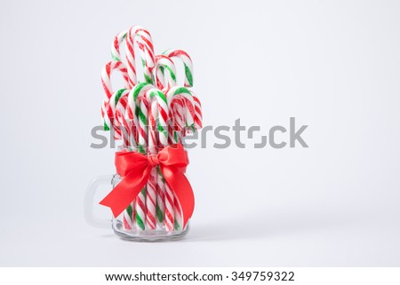 Mint hard candy cane striped in jar Christmas colors and snow man isolated on a white background. Closeup. - stock photo