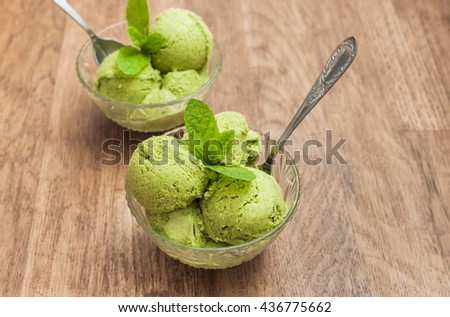 Mint ice cream in glass bowls on wooden background - stock photo