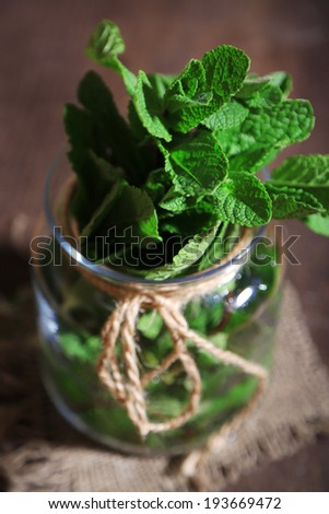 Mint in glass jar on wooden background - stock photo