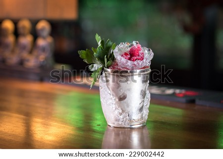 Mint julep cocktail with raspberry served in frozen metal cup on the bar - stock photo