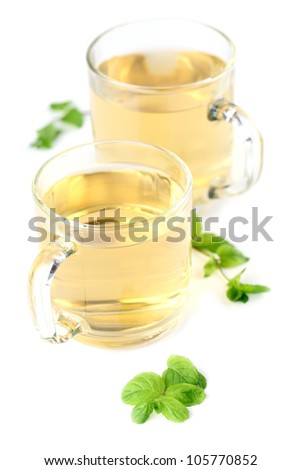 Mint leaf and freshly made mint tea in glass cups isolated on white background. Shallow dof, focus on mint
