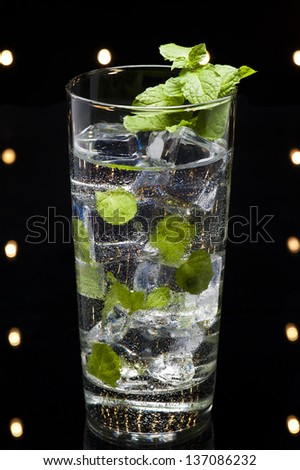Mint Mojito cocktail in an disco setting - stock photo