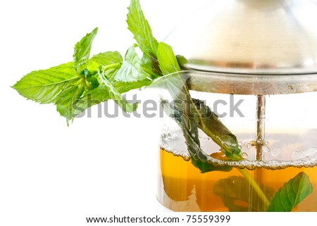 mint tea in a teapot and a bundle of mint