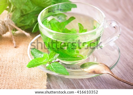 Mint tea in a transparent glass cup on the table - stock photo