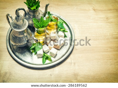 Mint tea with traditional arabic delight. Oriental hospitality concept. Holidays table setting. Vintage style toned picture. Selective focus - stock photo