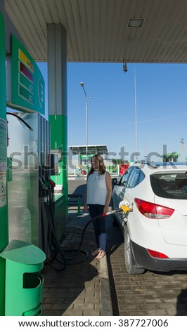 Miory, Belarus - July 25, 2015: the girl at gas station fills in gasoline in the car. - stock photo