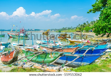 MIRISSA, SRI LANKA - DECEMBER 3, 2016: The old catamaran boats at shore of the fisheries harbor and the amphibious excavator, dredging the port's bed on background, on December 3 in Mirissa.