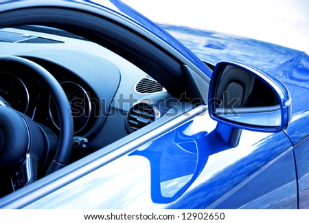 Mirror and dashboard on blue sports car - stock photo