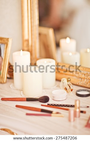 Mirror, candles, powder, puff, eyeliner and other cosmetics on the table - stock photo